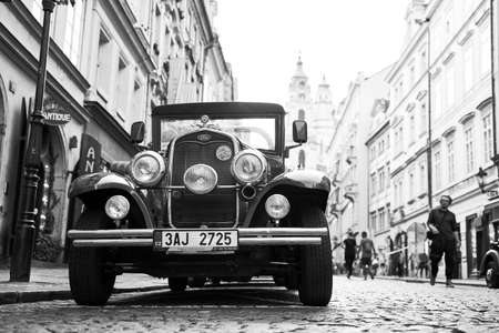 Vintage Ford car used for tourist attraction parked on the Mostecka street in historical Mala Strana district. Black and white image.