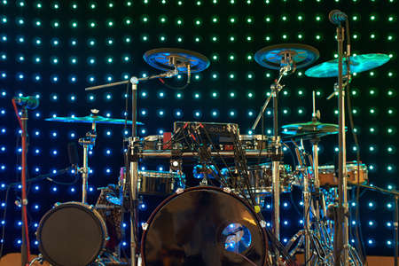 Drum kit with different types of drums on the stage with lights on the background in colorful light