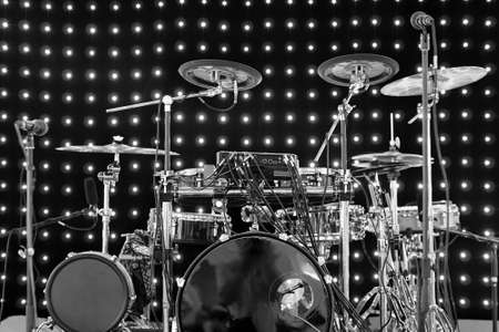 Drum kit with different types of drums on the stage with lights on the background in black and white
