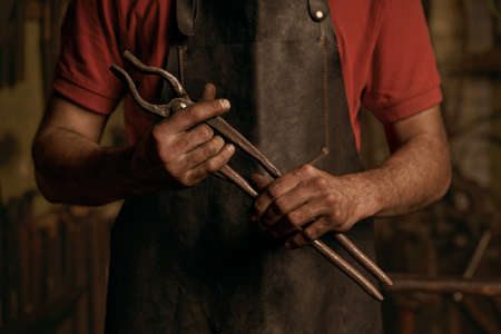 Blacksmith with metal tongs in smithy portrait