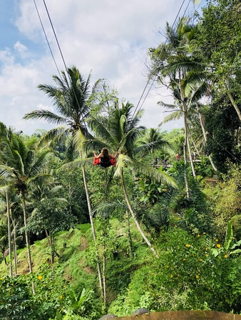 A female tourist on a high swing over a paddy field in Bali