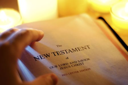 turning page: New Testament by Candlelight Stock Photo