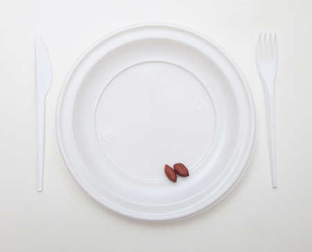 White disposable dishware set Fork, Knife and Peanut Banco de Imagens