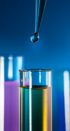 Laboratory pipette with a drop of substance over test tubes on blue background