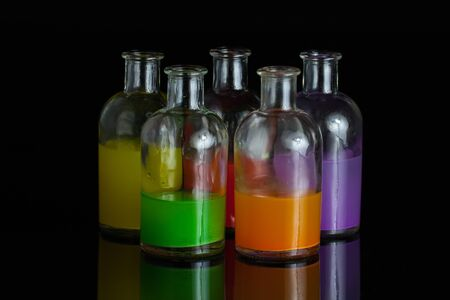 Apothecary, laboratory bottles with colored liquid with reflection