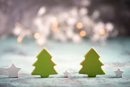 Christmas trees and star with blury lights in the background, greeting card, empty copy space