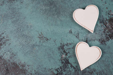 Two white hearts on a blue textured shabby background, empty space for text 写真素材