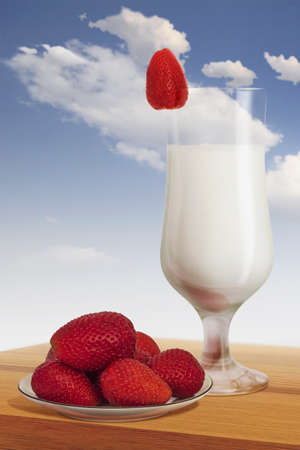 plateful: Plateful of strawberries with glass of milk, on a wooden table, with a blue skies and small puffy clouds in the background  Isolated image, equipped   Stock Photo