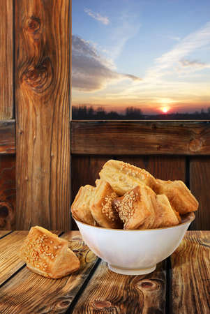 Square puff croissant pastry Zu-Zu, in white porcelain bowl, isolated with precise clipping pat, placed in wooden rustic farm ambient, with a sunset, dusk cloudy sky in the background window  photo