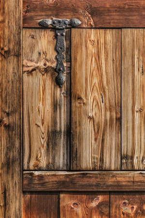 Antique rustic Pine wooden door detail, with wrought iron hinge  photo
