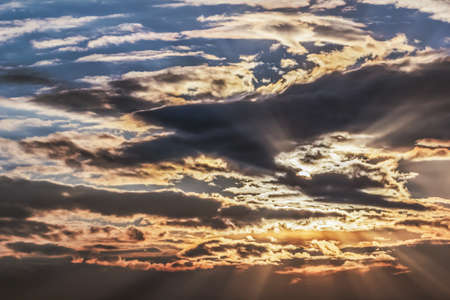 transient: Dramatic cloudy sunset skies - Stratocumulus Translucidus with hidden sun, and array of spread sunbeams  Stock Photo
