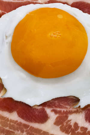 Sunny side up egg yolk with bacon slices, detail  photo