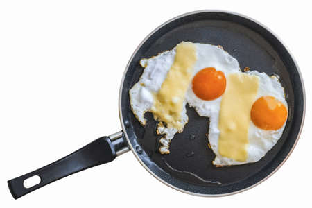 Photograph of pair of sunny side up eggs in a Teflon frying pan, isolated on white, equipped with clipping path  photo