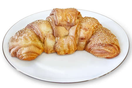 Photograph of croissant puff pastry roll, sprinkled with Sesame seeds, placed on white porcelain plate  The image is isolated on white background, and supported with corresponding clipping path  photo