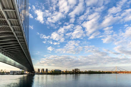 Panoramic photograph of Belgrade and Sava river with the Bridge Over Ada and the New Railroad bridge in the distance, made at dusk, from the lower tip of Ada Ciganlija river isle   photo
