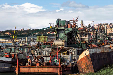 Photograph of Belgrade urban panorama with old, decommissioned, abandoned towboats, barges and dredgers at the ship junkyard on Sava river - Belgrade - Serbia   photo
