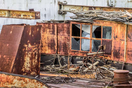 scrapped: an old, decommissioned, scrapped rusty barge -