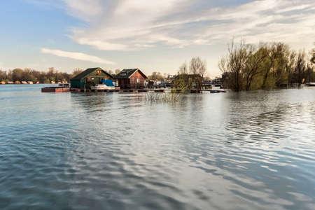 cielos azules: Fotograf�a temprana primavera disparo en la oscuridad del nivel de agua del r�o Sava resucitado, con casas flotantes a lo largo de sus orillas, los �rboles sin hojas toldos, y el cielo azul con nubes blancas