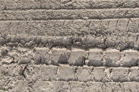 sandy soil: Photograph of a tire track left in wet sandy soil