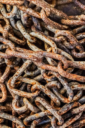 entropy: Very old, obsolete, weathered, badly corroded, heap of rusty chain links, covered with layers of decomposed metal crust and scales of rust peeling off