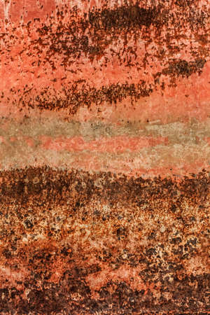 Old, obsolete, badly corroded rusty metal plate, covered with cracked, decomposed layers of red, anti corrosive paint and rust  photo