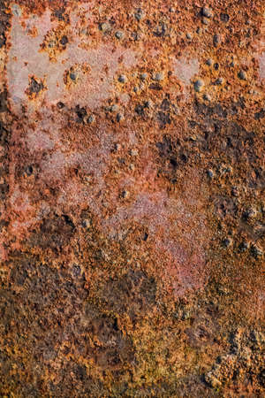 scrapped: Old, scrapped, badly corroded rusty metal riveted plates, covered with cracked, decomposed layers of red anti-corrosive paint, tar and rust