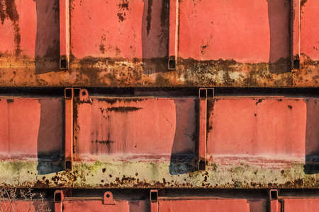 floaters: Old, scrapped, badly corroded, rusty raft metal floaters, covered with layers of damaged red anti-corrosive paint, rust and moss  Stock Photo