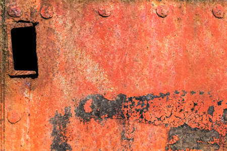 Old, scrapped, badly corroded rusty metal riveted plate, covered with cracked, decomposed layers of red anti-corrosive paint, tar and rust  photo