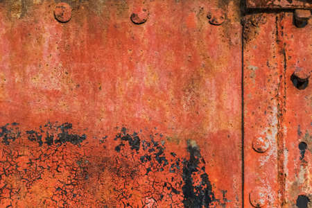 entropy: Old, scrapped, badly corroded rusty metal riveted plates, covered with cracked, decomposed layers of red anti-corrosive paint, tar and rust