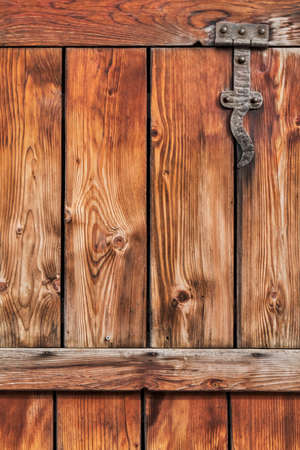 Photograph of old, weathered rustic Pine wooden door, with wrought iron hinges - detail  photo