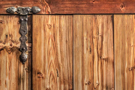 interstice: Photograph of old, weathered, rustic, knotted Pine wooden door, with wrought iron hinges - detail