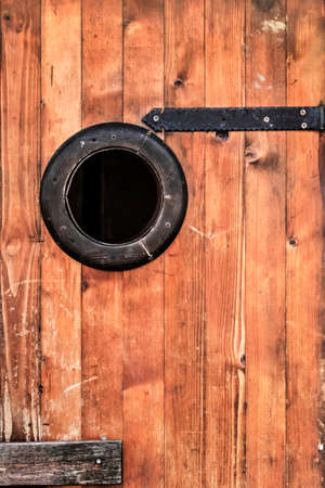 Photograph of old, weathered, rustic, knotted Pine wooden hut door, with wrought iron hinges - detail  photo