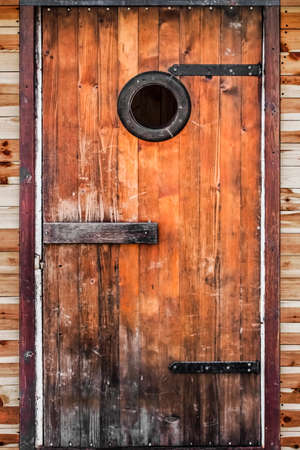 Photograph of old, weathered, rustic, knotted Pine wooden hut door, with wrought iron hinges  photo