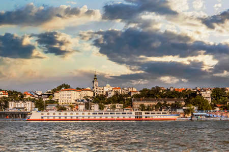 Panorama of Belgrade, Republic of Serbia, viewed from Sava river perspective, with St  Michael s Cathedral bell tower, Tourist port, and downtown cloudy skyline   photo