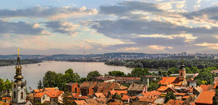 Photograph of panoramic view from Gardos on town of Zemun at sunset, with Saint Nicholas church baroque bell tower and river Danube  Zemun, Belgrade, Republic of Serbia