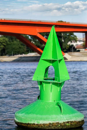 downstream: Green metal navigation nautical buoy, anchored at the downstream approach to the Gazelle bridge, on Sava river - Belgrade - Serbia   Stock Photo