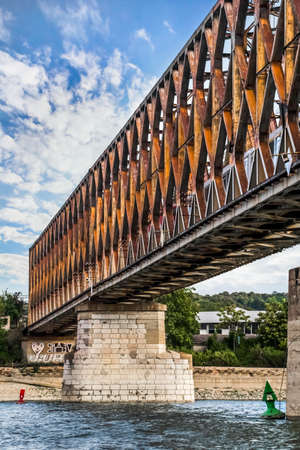 struts: Belgrade s Old railway bridge over Sava river, with details of bridge stone base, old rusty steel girder construction and truss framework, with train locomotive and passenger coach, crossing the bridge