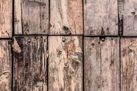 patched: Very old, weathered, rotten floorboards, fixed and patched with planks of different origin, with uneven in-between gaps, large wood knots, and round head machine screws embedded - detail  Stock Photo