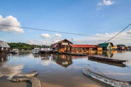 cielos azules: Resucitado nivel del agua del r�o Sava, con casas flotantes a lo largo de sus orillas, los �rboles verdes doseles y cielo azul con nubes blancas mullidas
