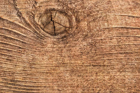 Photograph of old, roughly treated, weathered, cracked floorboard, with large wood knot