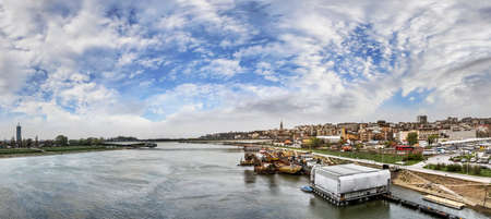 watersmeet: Cloudy skyline of New and Old Belgrade downtown, with Bus station, floating raft night club, old vessels winter shelter, Branko s bridge, and mouth of the river Sava with Danube in the distance