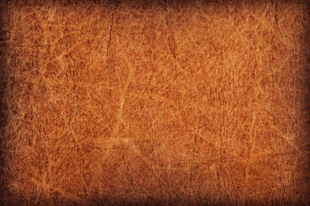 Photograph of old, weathered, rough, creased, coarse grained, exfoliated Brown leather, vignette grunge texture sample.