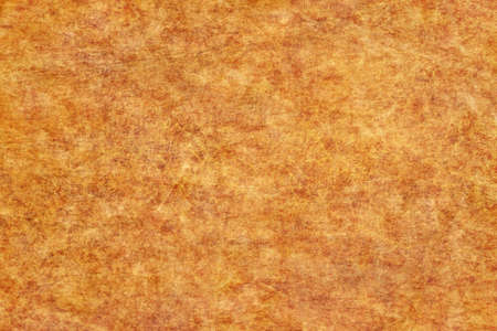 Photograph of old, Yellow-ocher animal skin parchment, coarse grained, grunge texture. Stock Photo