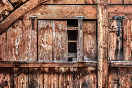 Photograph of an old, damaged rustic Pine wooden door, with wrought iron hinges - detail. photo