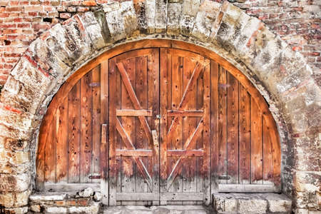 interstice: Old brick-stone Rampart with rustic Pine wood Arsenal Door, secured with padlock.