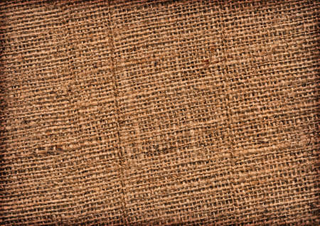 roughly: Photograph of roughly woven, extra coarse grain, burlap vignette grunge texture.