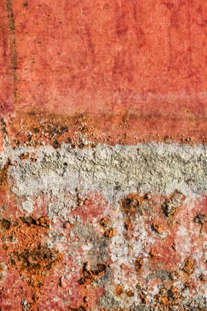 entropy: Old, obsolete, badly corroded river raft hut floater metal surface, covered with layer of cement roughcast, cracked decomposed red paint and rust.