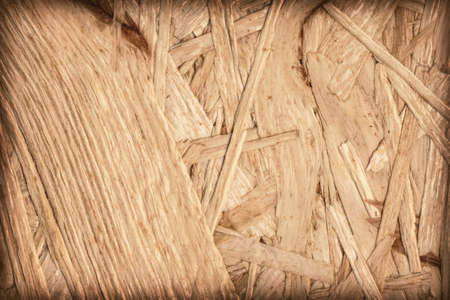 chipboard: Wooden chipboard, rough, extra coarse surface vignette grunge texture. Stock Photo