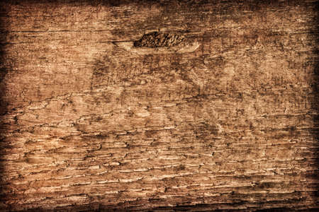 Photograph of old, roughly treated, weathered, cracked, knotted Pine plank, vignette grunge texture. photo