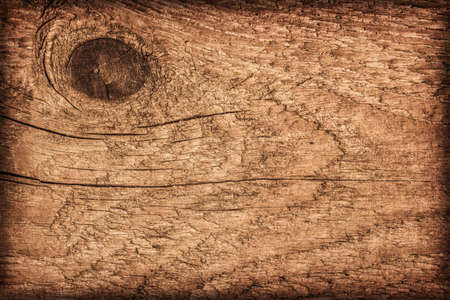 Photograph of old, roughly treated, weathered, cracked, knotted Pine plank, vignette grunge texture. Stock Photo